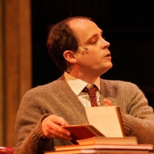 A man in a brown cardigan opening a large book.